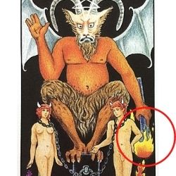 悪魔の左手の下に向けた松明(たいまつ)